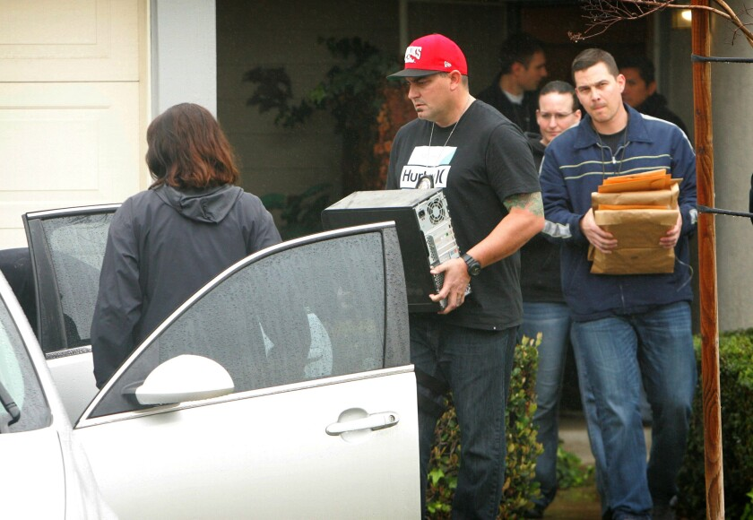 FBI and Homeland Security investigators remove a computer and other materials from the Corona home of Syed Raheel Farook.
