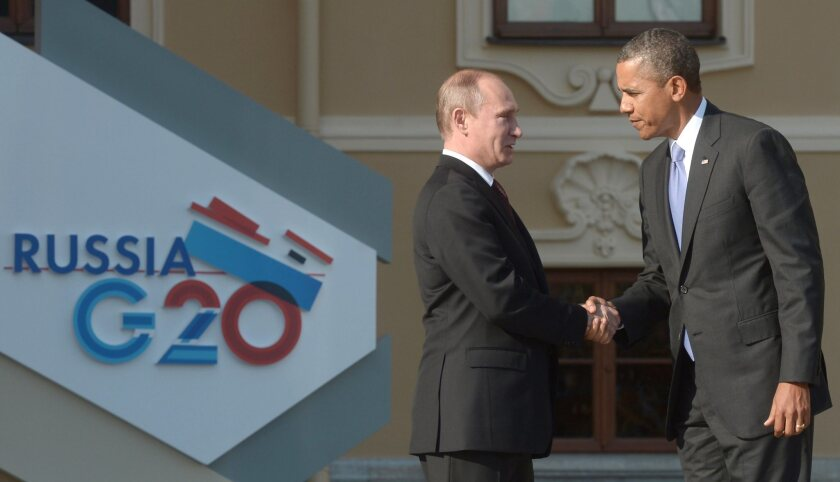 """Russian President Vladimir Putin welcomes President Obama to St. Petersburg in September in a brief encounter ahead of the G20 summit. Two Italian newspapers reported Tuesday that the Russian hosts included """"Trojan horse"""" data surveillance devices in the gift bags given to all G20 summit delegates."""