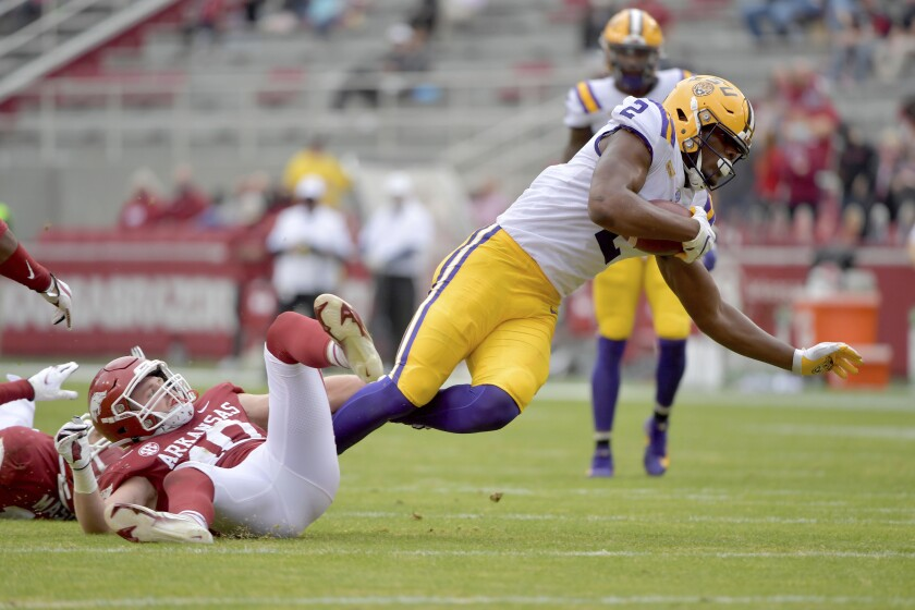 LSU tight end Arik Gilbert (2) is tripped up by Arkansas defender Bumper Pool (10) during the first half of an NCAA college football game Saturday, Nov. 21, 2020, in Fayetteville, Ark. (AP Photo/Michael Woods)