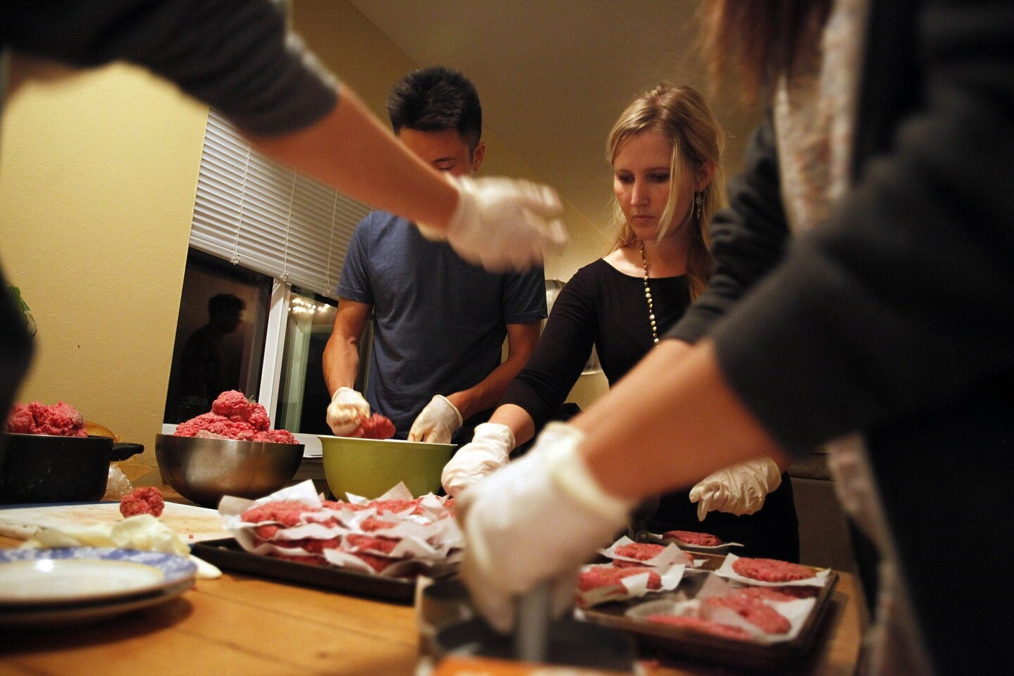 Students from UC Santa Barbara in Isla Vista make hamburgers in a leased building known as the Jesus Burgers house. After service, the grill is fired up.