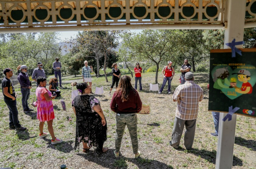 Community members from different political viewpoints gather in a circle during a bridge-building exercise in a park