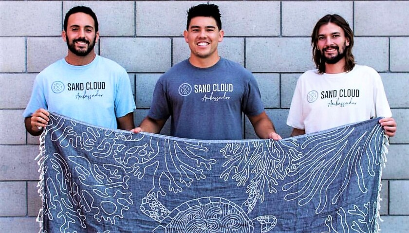 The co-founders of Sand Cloud, from left, Brandon Leibel, Steven Ford and Bruno Aschidamini, display one of the lightweight, sand-resistant beach towels that their company manufactures.