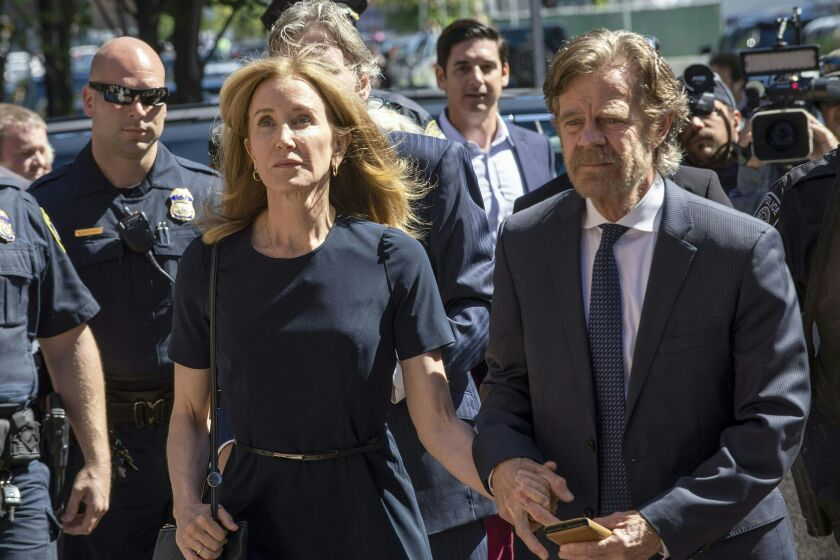 Actress Felicity Huffman, escorted by her husband William H. Macy, makes her way to the entrance of the John Joseph Moakley United States Courthouse September 13, 2019 in Boston, where she will be sentenced for her role in the College Admissions scandal. - Huffman, one of the defendants charged in the college admissions cheating scandal, is scheduled to be sentenced for paying $15,000 to inflate her daughters SAT scores, a crime she said she committed trying to be a good parent. (Photo by Joseph Prezioso / AFP) (Photo credit should read JOSEPH PREZIOSO/AFP/Getty Images)