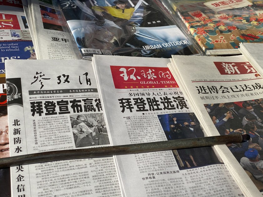 """Newspaper front-page with the headlines """"Biden wins"""" are displayed at newsstand on Beijing, China, Monday, Nov. 9, 2020. As Asia comes to terms with the reality of a Joe Biden administration, relief and hopes of economic and environmental revival jostle with needling anxiety and fears of inattention. (AP Photo/Ng Han Guan)"""