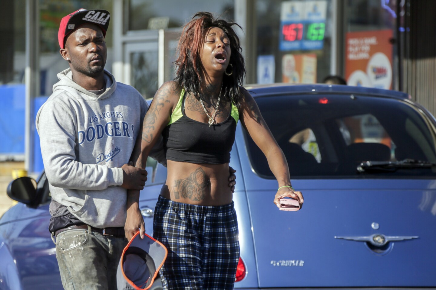 Grieving stepfather Leonard Grant, 27, left, and Ebony Newman, 27, mother of 9-year-old Travon Williams in front of the liquor store where the shooting occurred.