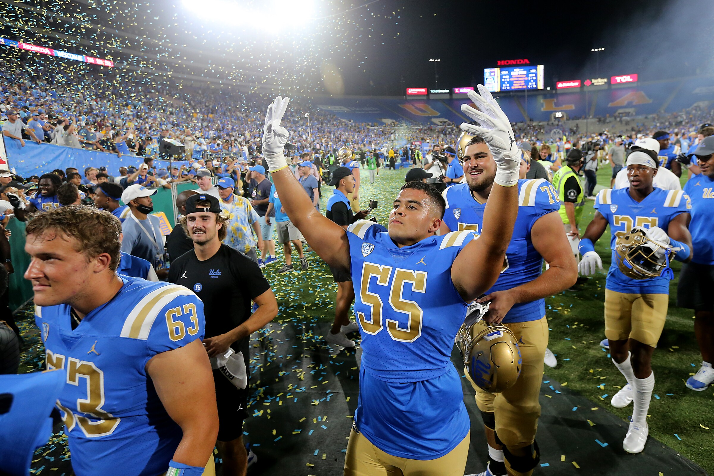 UCLA defensive lineman Tyler Kiehne holds up his hands while walking off the field.