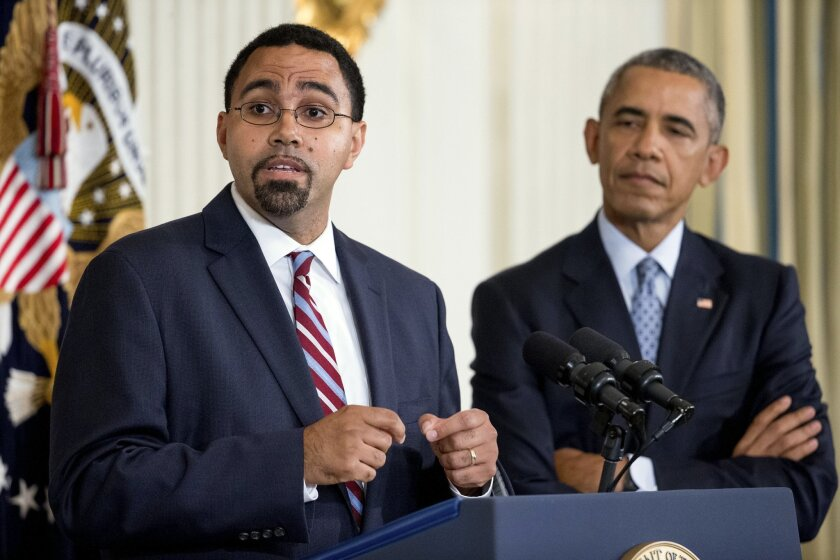 Senior Education Department official, John King Jr., left, accompanied by President Barack Obama, speaks in the State Dining Room of the White House in Washington, Friday, Oct. 2, 2015, after Obama announced that Education Secretary Arne Duncan will be stepping down in December after 7 years in the