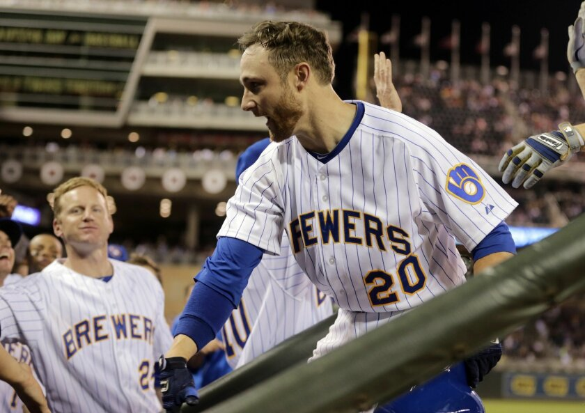Milwaukee Brewers' Jonathan Lucroy is welcomed in the dugout following his two-run home run off Minnesota Twins pitcher Jared Burton in the ninth inning of a baseball game, Thursday, June 5, 2014, in Minneapolis. The Brewers won 8-5. (AP Photo/Jim Mone)
