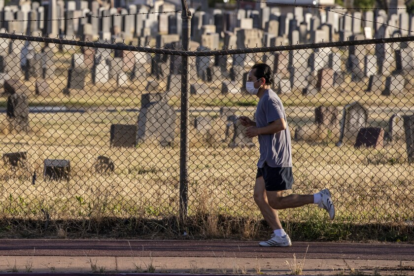 A jogger wearing a mask runs past Evergreen Cemetery in Boyle Heights on Tuesday.