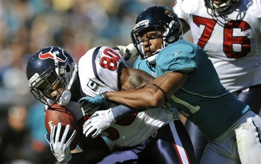 Houston Texans wide receiver Andre Johnson (80) bobbles the ball for an incomplete pass while being defended by Jacksonville Jaguars cornerback Derek Cox (21) in the first quarter of an NFL football game in, Sunday, Nov. 14, 2010, Jacksonville, Fla. (AP Photo/Stephen Morton)