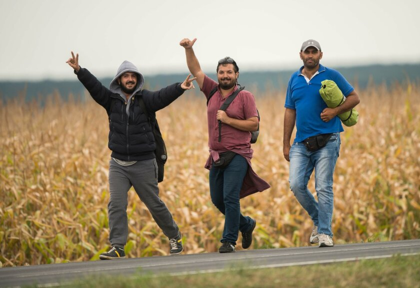 Migrants make their way along a road after crossing the border between Austria and Hungary near Heiligenkreuz, about 180 kms (110 miles) south of Vienna, Austria, Saturday, Sept. 19, 2015. Thousands of migrants who had been stuck for days in southeastern Europe started arriving in Austria early Saturday after Hungary escorted them to the border. (AP Photo/Christian Bruna)