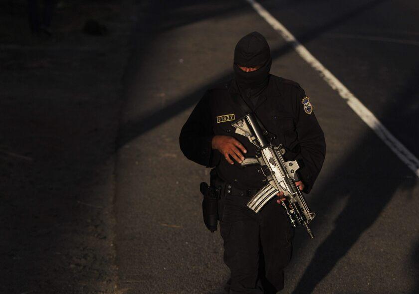Un agente de la Policía Nacional Civil (PNC) vigila las cercanías de la escena de un crimen, en un estacionamiento de furgones, en Quezaltepeque.