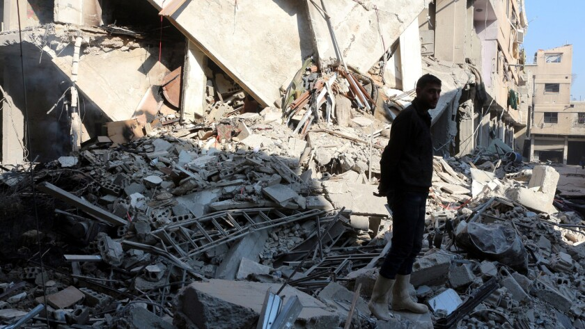 A Syrian man stands amid the debris of a building destroyed in a Russian airstrike in eastern Ghouta in Damascus on Dec. 25, 2015.