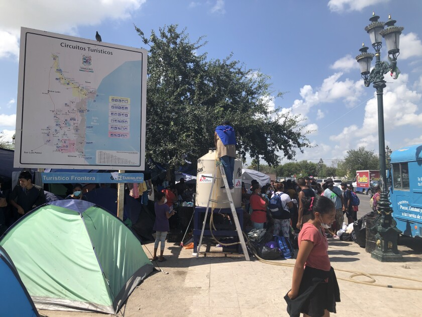 A tourism billboard amid the migrant camp in Reynosa, Mexico.