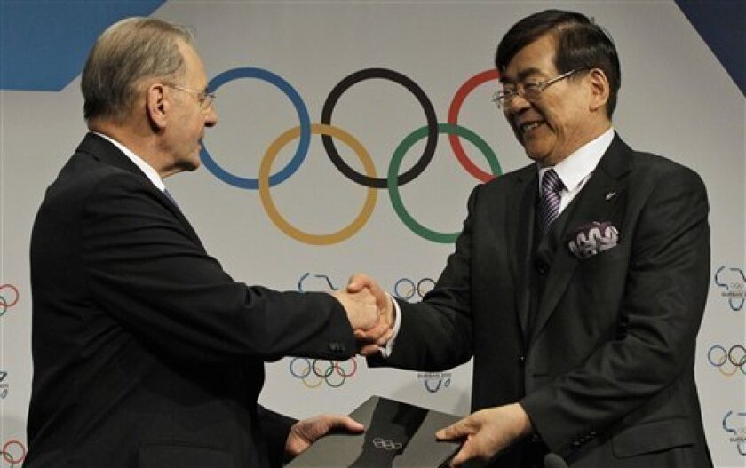 International Olympic Committee President Jacques Rogge, left, shakes hand with South Korea's Olympic Bid chairman Cho Yang-ho, right, after a signing the host city contract for the 2018 Winter Olympics in Durban, South Africa, Wednesday July 6, 2011. The South Korean city of Pyeongchang was awarded the 2018 Winter Olympics on Wednesday, taking the games to a new territory in Asia after failing in two previous attempts. (AP Photo/Themba Hadebe)