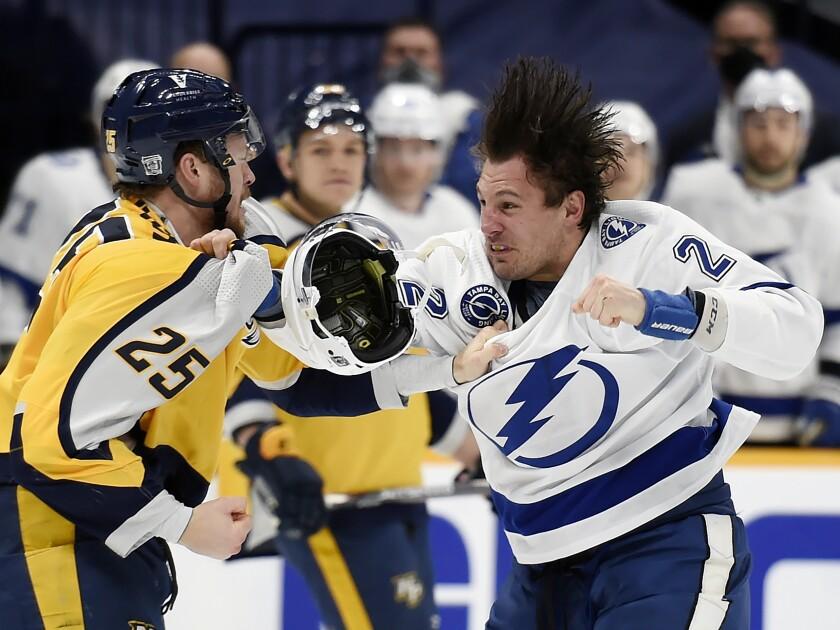 Nashville Predators right wing Mathieu Olivier (25) fights with Tampa Bay Lightning defenseman Luke Schenn (2) during the first period of an NHL hockey game Monday, Feb. 8, 2021, in Nashville, Tenn. (AP Photo/Mark Zaleski)