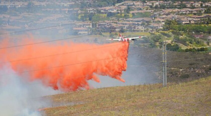 An air tanker drops retardant on the north edge of Santaluz, with 4S Ranch in background in the Rancho Santa Fe area on May 13, 2014. As of 8:30 a.m. May 14, the fire has burned about 1,550 acres and is 25 percent contained. (Photo by Leo Nicolet)