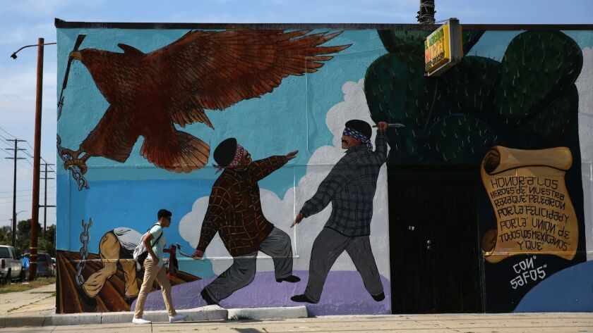 "LOS ANGELES, CA-MAY 14, 2019: A person walks past the ""El Mercadito Market"" mural on May 14, 2019, i"