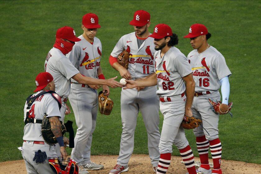 El pitcher de los Cardenales de San Luis Daniel Ponce de León entrega la pelota al manager Mike Shildt
