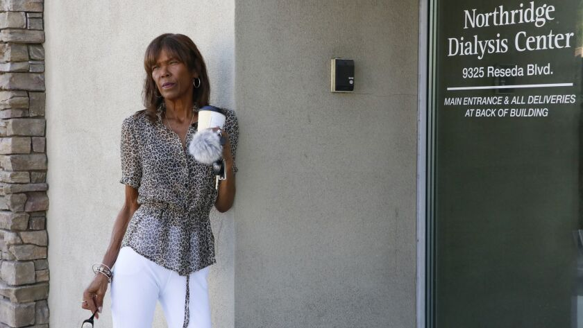 Dialysis patient Tangi Foster stands at the entrance to the clinic owned by U.S. Renal Care where she receives treatment several times a week.