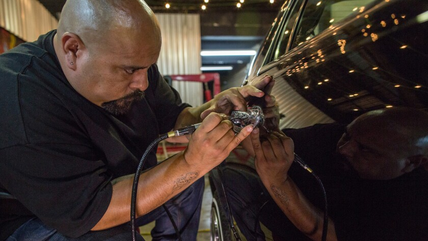 Jose Jesus engraves a door handle during a gathering of lowrider enthusiasts in Sao Paulo, Brazil.