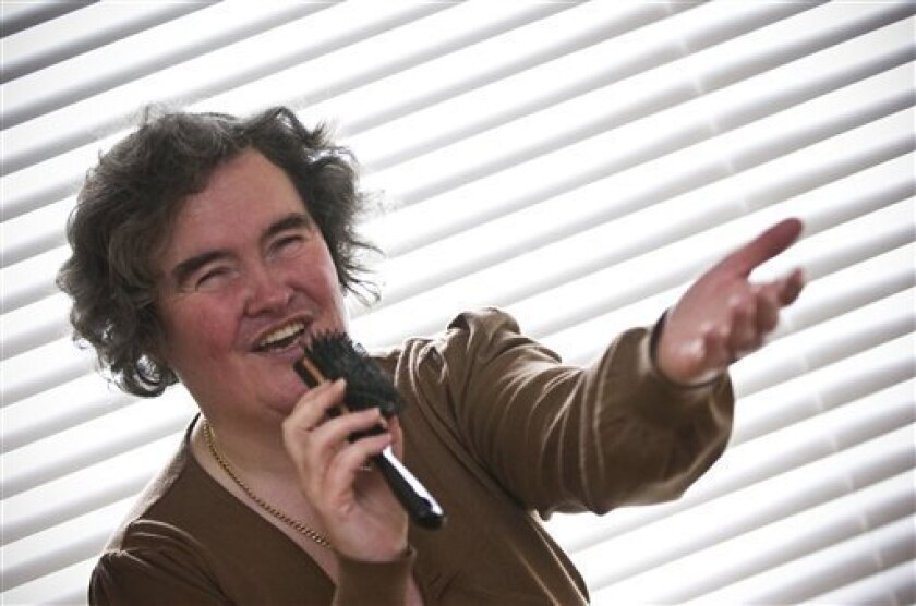 "Susan Boyle, who's performance on the television show ""Britain's Got Talent"" wowed the judges, poses singing with a hairbrush at her home in Blackburn, Scotland, Thursday April 16, 2009. The frumpy 47-year-old, who says she's never been kissed, has gained celebrity fans and millions of admirers - i"