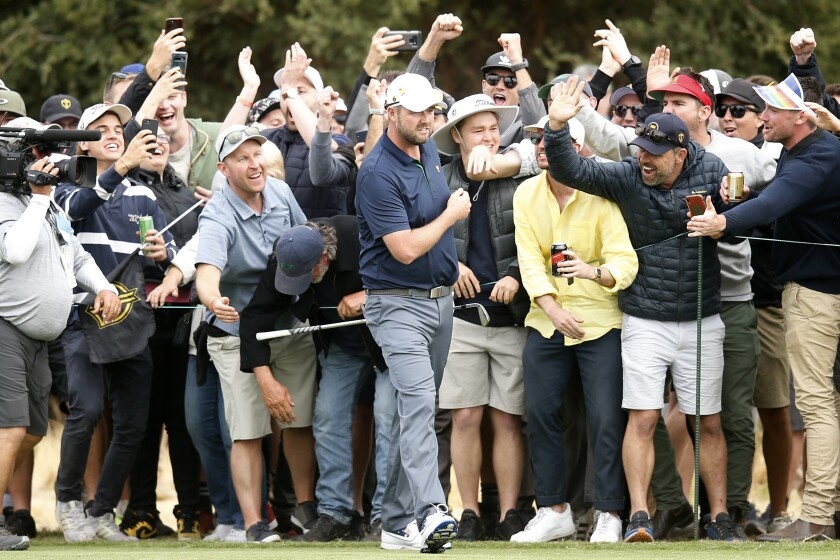 Australian Marc Leishman of the International team celebrates with fans after his shot on the 18th hole during a foursome match on Dec. 14 at the Presidents Cup.
