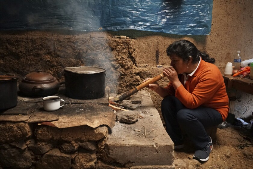 The future first lady of Peru, Lilia Paredes, 48, blows air through a hollow reed to get a fire going in her wood-burning stove in her adobe home in the rural hamlet of Chugur, Peru, Thursday, July 22, 2021. Her husband, leftist Pedro Castillo catapulted from unknown to president-elect with the support of the country's poor and rural citizens, many of whom identify with the struggles the teacher has faced. (AP Photo/Franklin Briceno)