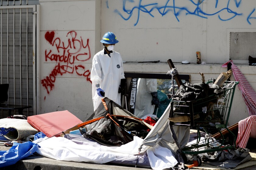 An L.A. sanitation worker cleans up around a  homeless encampment on a sidewalk in South Los Angeles in 2018.