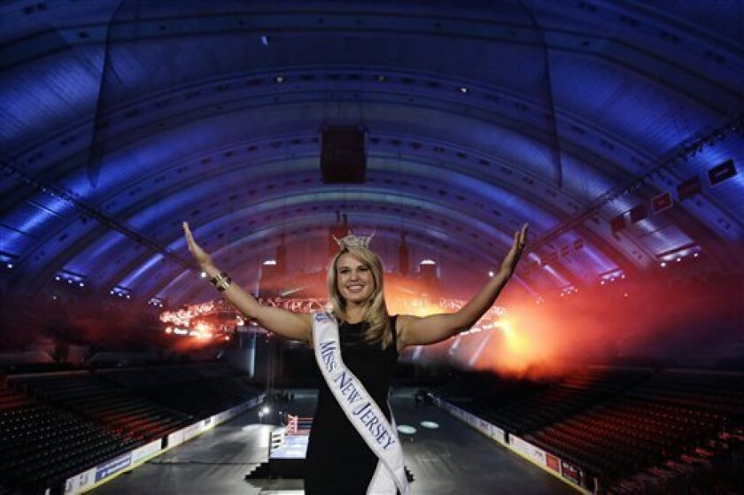 Miss New Jersey for 2012 in the Miss America pageant, Lindsey Petrosh, of Egg Harbor City, N.J., gestures for photographs in Atlantic City's Boardwalk Hall, Thursday, Feb. 14, 2013, in Atlantic City, after New Jersey Lt. Gov. Kim Guadagno announced that the Miss America pageant is returning to Atla