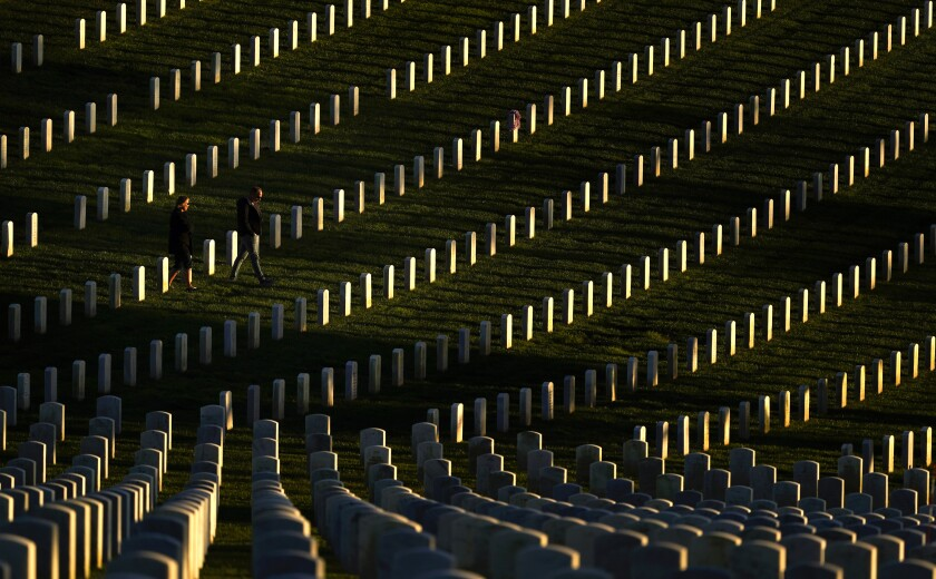 A couple walks among graves at Fort Rosecrans National Cemetery on Veterans Day in San Diego.