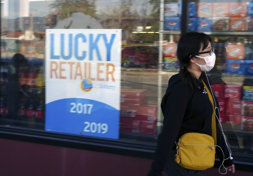 A pedestrian wears a protective mask in Alhambra, Calif., Friday, Jan. 31, 2020. As China grapples with the growing coronavirus outbreak, Chinese people in the Los Angeles area, home to the third-largest Chinese immigrant population in the United States, are encountering a cultural disconnect as they brace for a possible spread of the virus in their adopted homeland. (AP Photo/Damian Dovarganes)