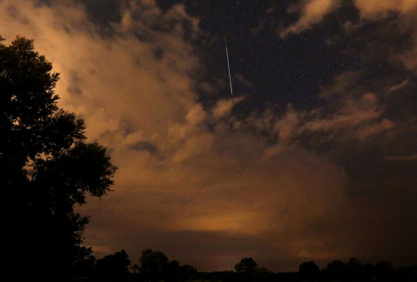 A meteor streaks through a bare patch of sky above Gainesville, Fla., during the annual Perseid meteor shower on Thursday, Aug. 13, 2015.