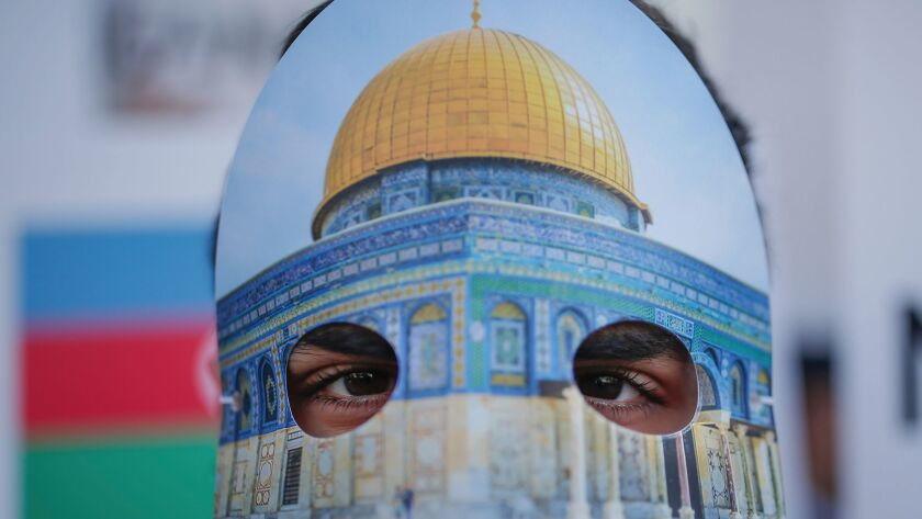 Protesters wearing masks with Jerusalem's Dome of the Rock Mosque, participate in a rally against U.
