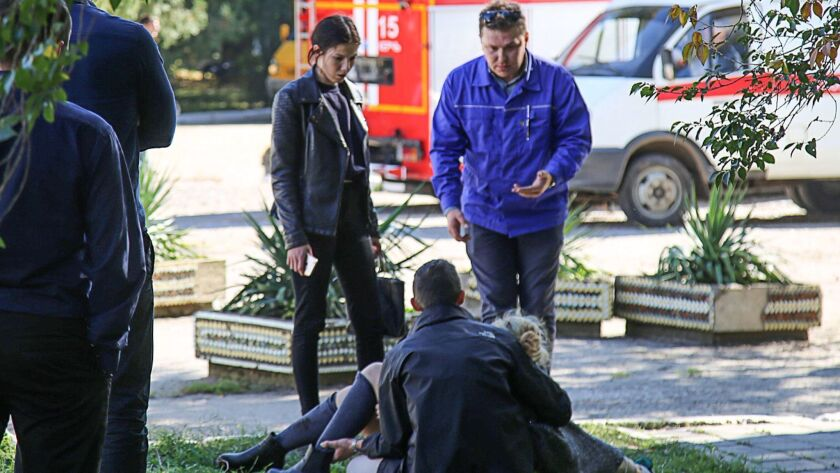 A man holds an injured victim of an attack at a college in the city of Kerch in Crimea on Wednesday.