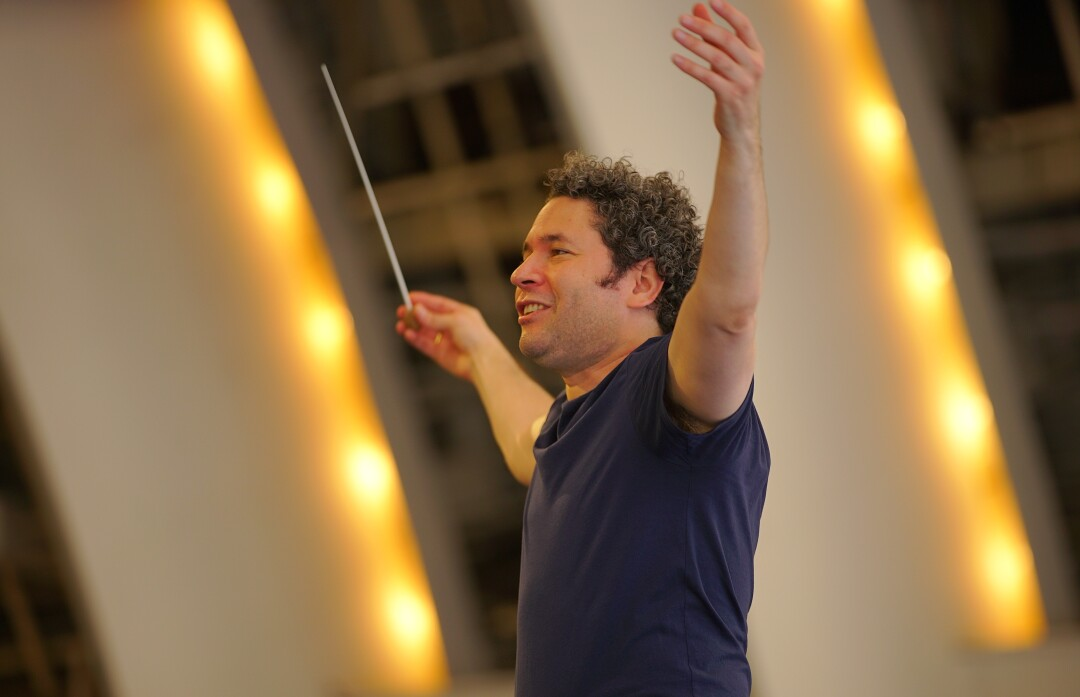 Dudamel, looking exultant, raises his arms with baton in hand