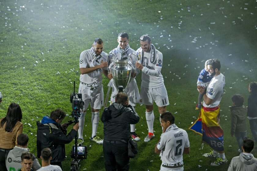 From left, Real Madrid's Karim Benzema, Cristiano Ronaldo and Gareth Bale pose for a photograph with the Champions League trophy at the Santiago Bernabeu Stadium in Madrid, Sunday, May 29, 2016. Tens of thousands of fans endured the rain to greet Real Madrid players as they returned home early Sund