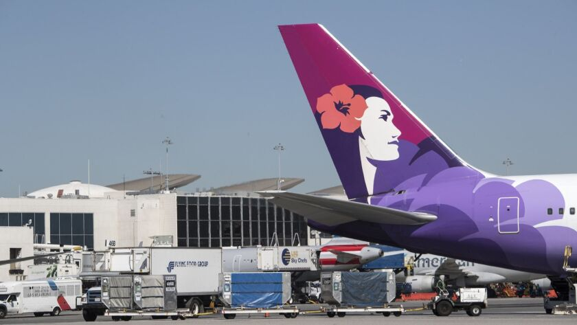 A Hawaiian Airlines aircraft waits on the tarmac at Los Angeles International Airport on March 28, 2018. The carrier raised fees by $5, to $30 for the first checked bag and $40 for the second.