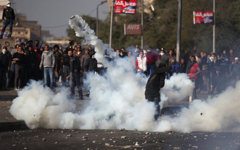 Egyptian protesters face off against riot police, unseen, near Tahrir Square in Cairo on Tuesday.