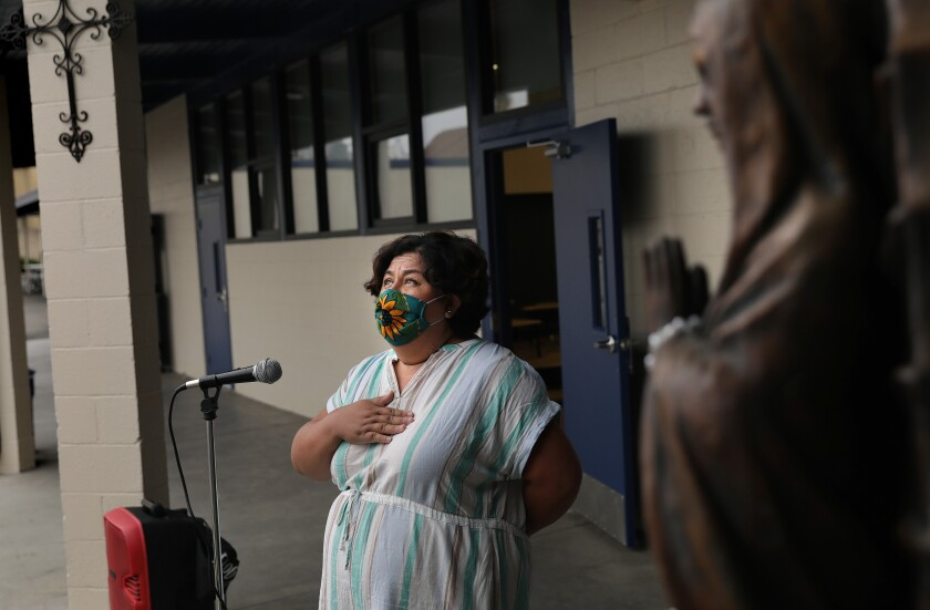 A masked woman recites the Pledge of Allegiance with her hand over her heart