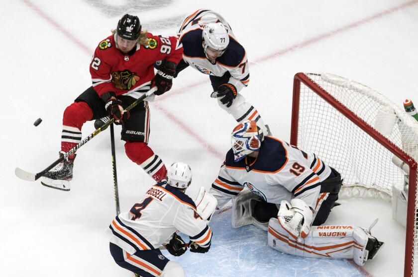 Edmonton Oilers goalie Mikko Koskinen (19) makes the save as Chicago Blackhawks' Alex Nylander (92) and Oilers' Oscar Klefbom (77) battle for the puck during the third period of an NHL hockey playoff game Friday, Aug. 7, 2020, in Edmonton, Alberta. (Jason Franson/Canadian Press via AP)