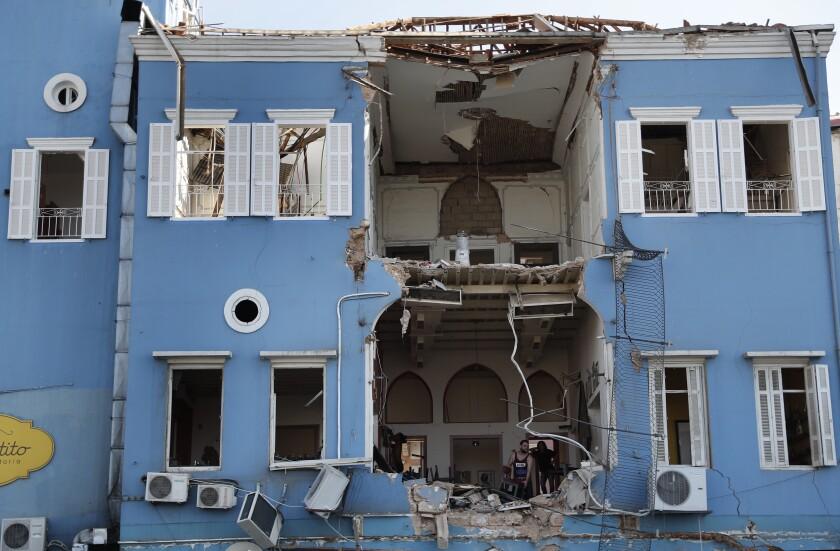 Trabajadores retiran escombros en un edificio dañado tras una explosión en Beirut, Líbano