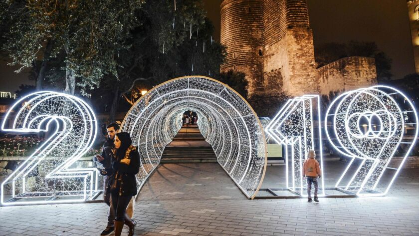 People walk past New Year decorations in front of the Maiden Tower this month in the old city of central Baku, Azerbaijan.