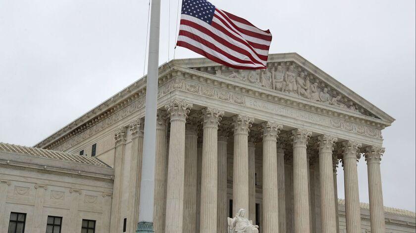 A U.S. flag flies at half-mast outside the U.S. Supreme Court on Sept. 30, 2018, in Washington, D.C.
