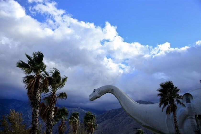 Dinny, a 150-foot long concrete apatosaurus, in Cabazon, against a backdrop of palm trees and a blue sky with white clouds.