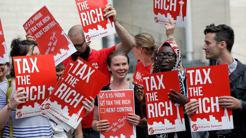 Demonstrators stand together as they wait for a Republican response to a new city income tax on the
