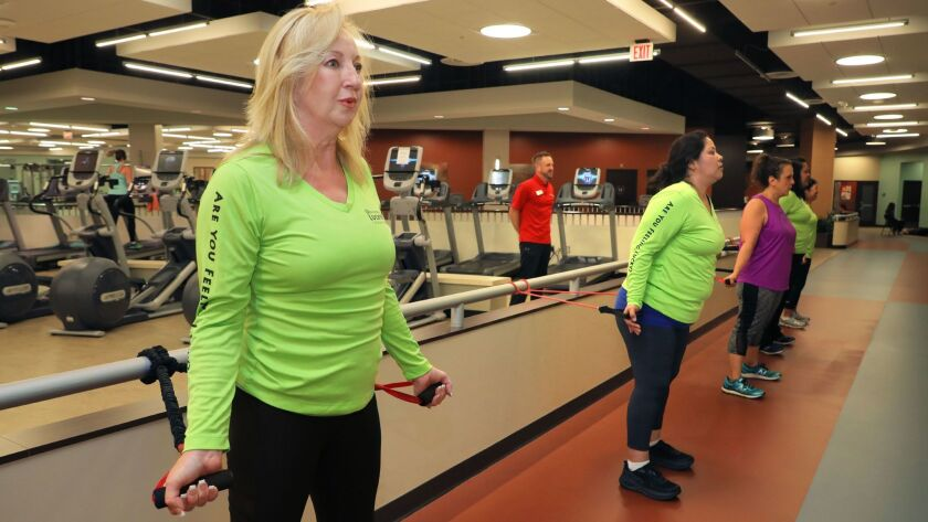 "Beth Thorp, at left, works out with the bands with other members of the ""Lucky 13"" who are former patients of Tri-City Medical Center chosen for its free six-month training program for the Carlsbad Half Marathon on Jan. 14."