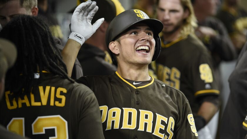 The Padres' Luis Urias is congratulated after hitting a two-run home run during the eighth inning of a baseball game against the Colorado Rockies at Petco Park on Aug, 31, 2018 in San Diego, California.