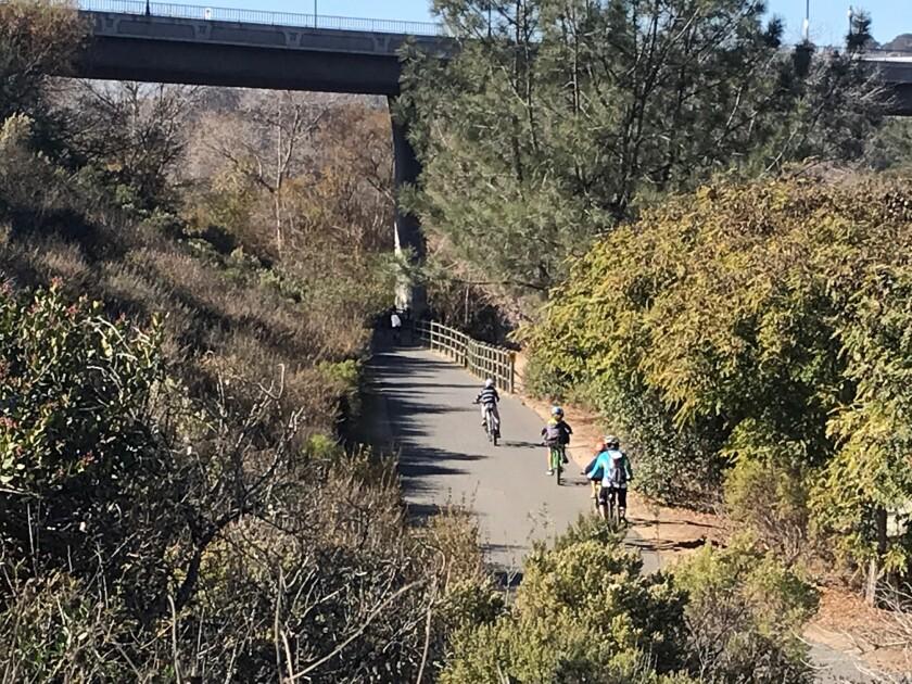 Cyclists ride on the SR-56 bike path through Carmel Valley.