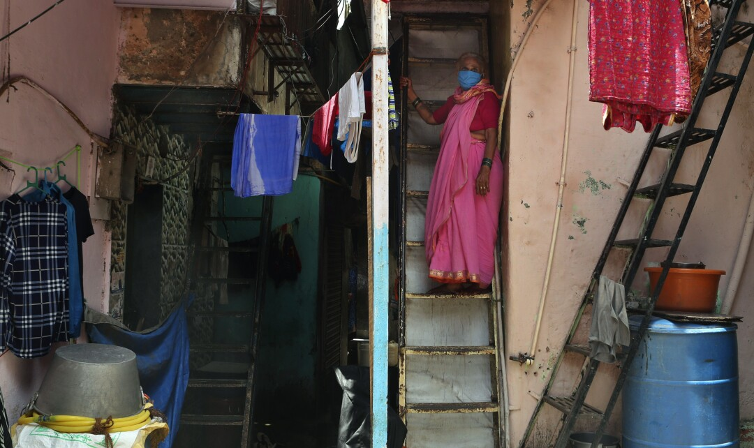 A woman wearing a mask stands on her staircase in Dharavi.